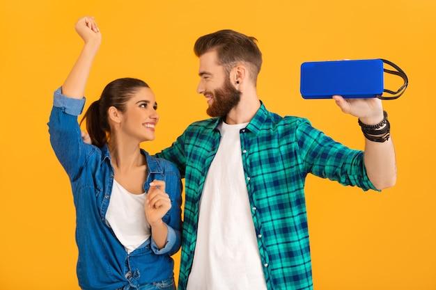 Lässiges junges paar, das einen drahtlosen lautsprecher hält und musik hört, die isoliert auf gelb tanzt
