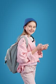 Lässiges kluges junges mädchen mit rucksack und mobilem gerät, das im smartphone während des schulbesuchs oder des colleges rollt