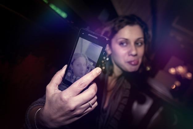 Lässiges porträt einer positiven emotionalen jungen frau im nachtrestaurantclub am tisch. frau nimmt selfie am telefon und sehr emotional. nachtleben im nachtstadtlebensstilkonzept. platz kopieren