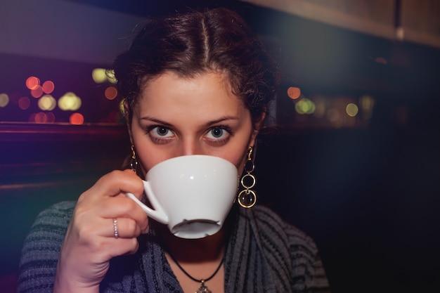Lässiges porträt einer positiven emotionalen jungen frau mit tasse kaffee im nachtrestaurantclub am tisch. nachtstadt-lifestyle-konzept. platz kopieren