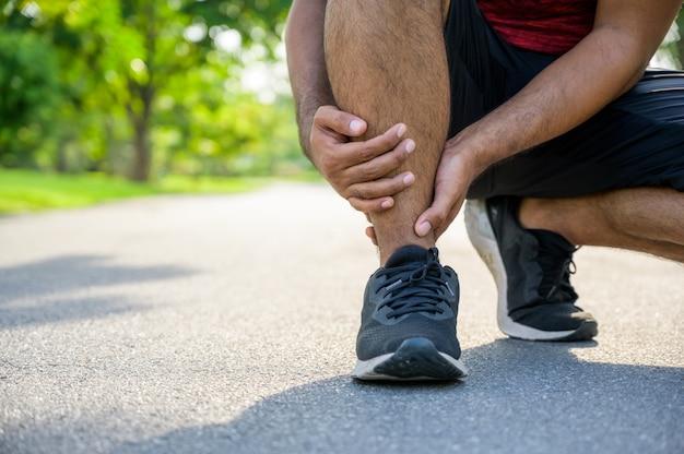Läufer, der fuß in den schmerz wegen des verstauchten knöchels berührt