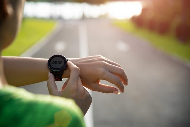 Läufer, der intelligente uhr vor dem laufen während des sonnenuntergangs einrichtet