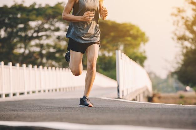 Läufer der jungen frau, der auf laufender straße im stadtpark läuft