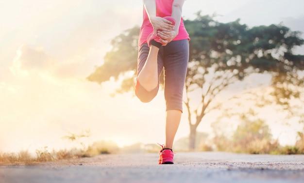 Läufer der jungen frau, der beine vor dem laufen an der ländlichen spur des sonnenuntergangs ausdehnt.