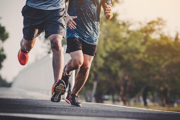 Läufer der jungen leute, der auf laufender straße im stadtpark läuft