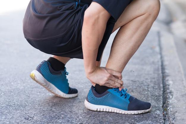 Läufer, der schmerzliche knöchel berührt. athlet läufer trainingsunfall.