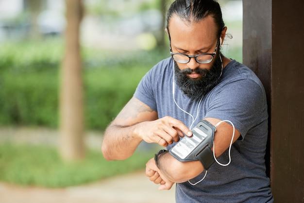 Läufer, der smartphone einschaltet