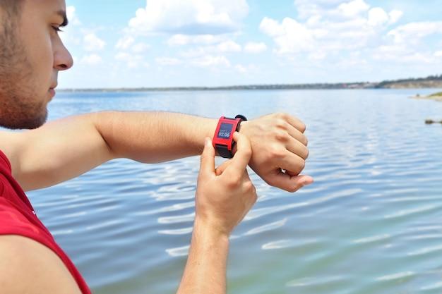 Läufer, der sport-smartwatch im freien betrachtet