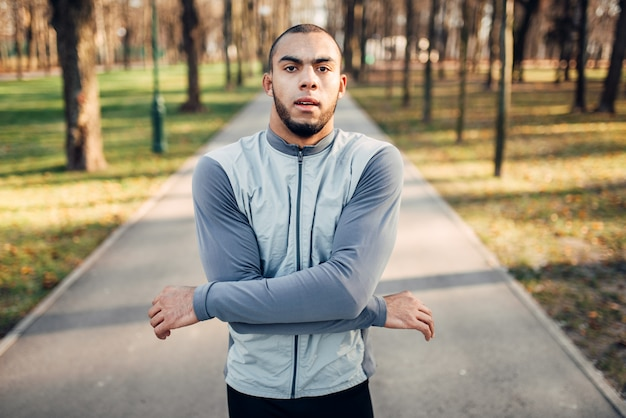 Läufer, der vor dem marathon marmoriert, aktiver, gesunder lebensstil. athlet am morgen fitness-training. jogger in sportbekleidung beim training im freien
