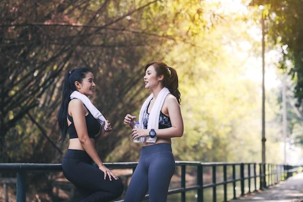 Läufer-fitnesspaar, das im stadtpark läuft, zwei frauen, die durch joggen trainieren