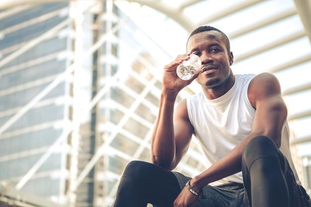 Läufer junger afroamerikanermann, der trinkwasser beim ausruhen nach dem training sitzt.