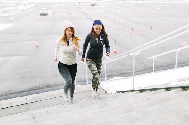 Läufer mit zwei frauen, der auf dem treppenhaus im winter rüttelt