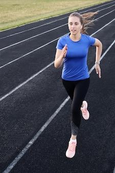 Läuferathlet, der auf der leichtathletikbahn läuft, trainiert ihr cardio im stadion. joggen im schnellen tempo für den wettbewerb.