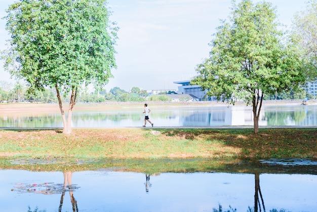 Läuferathlet des jungen mannes, der in einen park läuft