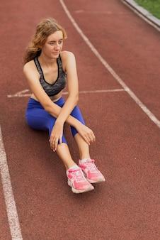 Läuferfrau, die am stadion sitzt