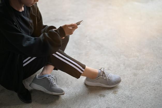 Läuferfrau, die einen handy mit dem ohrtelefon verwendet, das auf boden im haus vorläuft.