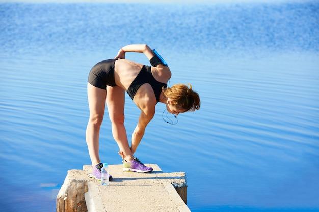 Läuferfrau, die in einen see im freien ausdehnt