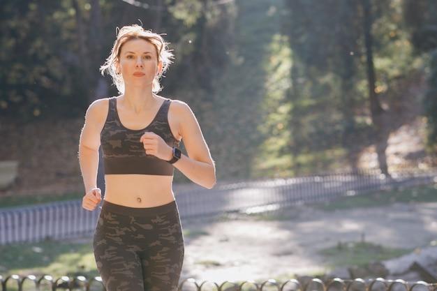 Läuferfrau fängt an, in tragenden kopfhörern zu laufen, die musik hören