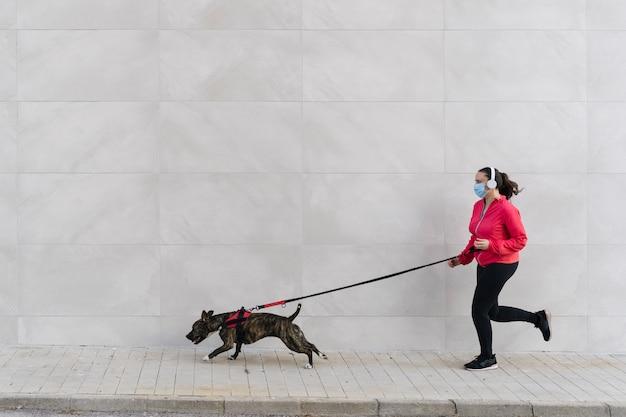 Läuferfrau mit ihrem hund, der medizinische maske trägt