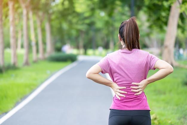 Läuferfrau mit rückenschmerzen aufgrund des piriformis-syndroms