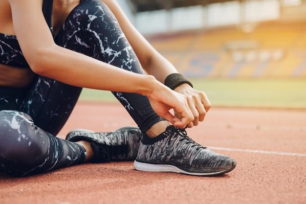 Läuferfrauen, die laufschuhspitzee binden werden, die zum rennen auf laufstrecke im stadion fertig werden