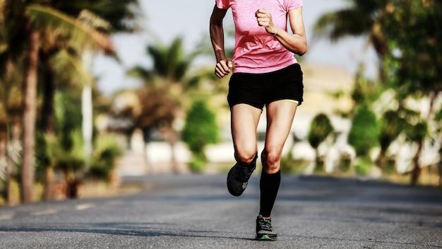 Läuferfüße, die auf asphaltstraßennahaufnahme laufen