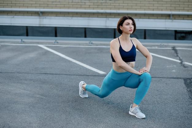 Läuferin, die sich nach einer laufeinheit in der stadt ausdehnt. junge sportfrau, die nach einem lauf pause macht.
