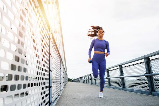 Läuferin mit starkem körper und beinen, die über die brücke laufen und trainieren.