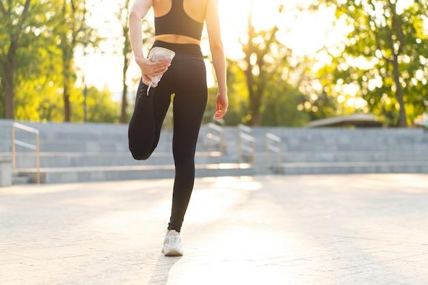 Läuferin streckt die beine vor dem sport im sommer parkmorgen mittleres alter athletische frau wärmt körper vor dem laufen kaukasische person aufwärmen joggen gekleidete weiße hemdshorts