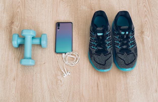 Läuferturnschuhe mit coolem smartphone, kopfhörern und kleinen hanteln in einem holz