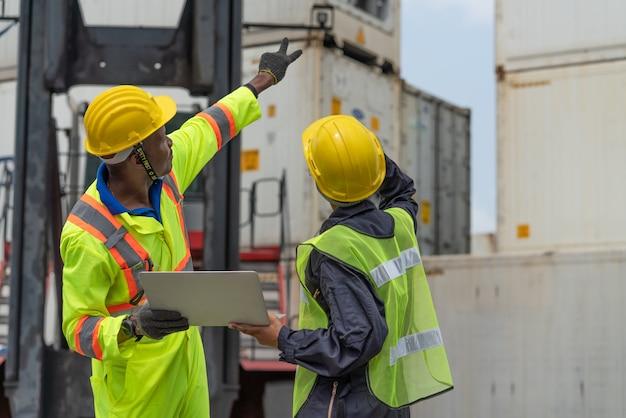 Lager logistikmitarbeiter mit laptop zeigen position container box vom frachtfrachtschiff bei frachtcontainer versand