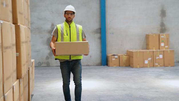Lagerarbeiter, der pappkarton im lager trägt. konzept für verpackungslieferung und lieferkettenmanagement.