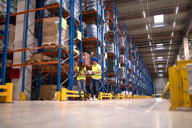 Lagerarbeiter diskutieren über logistik- und vertriebspakete auf dem markt