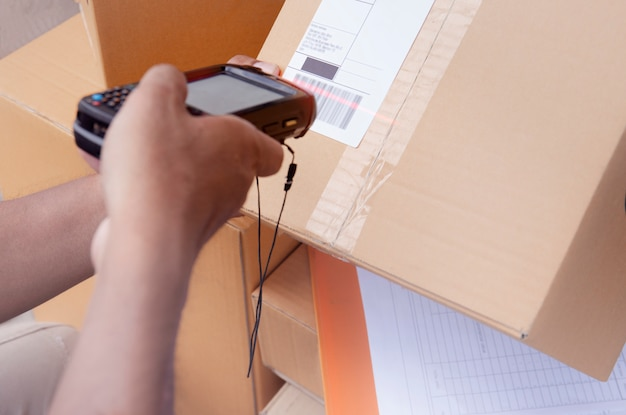 Lagerarbeiter halten barcodescanner mit dem scannen einer paketbox auf dem etikett für den versand an den kunden.