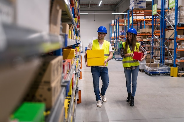 Lagerarbeiter mit helmen und reflektierenden jacken tragen kisten in einem großen distributionszentrum
