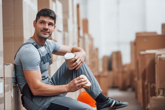 Lagerarbeiter sitzt und macht eine pause. isst sandwich und trinkt kaffee.