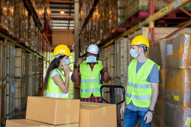 Lagerarbeiter tragen eine schutzmaske zum schutz vor covid-19 mit zwischenablage während der arbeit in einem lager.