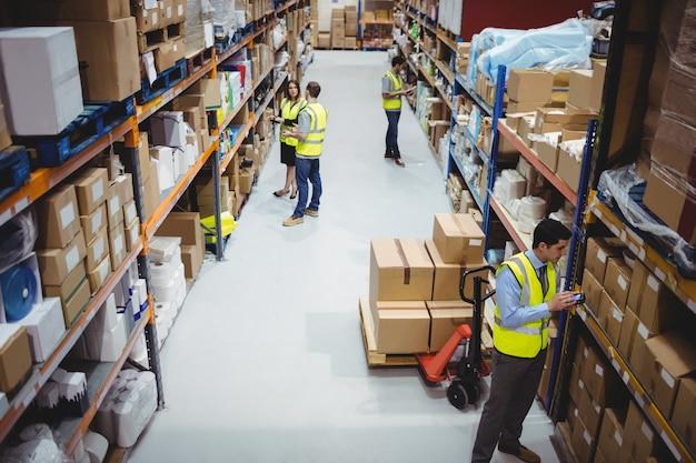 Lagerarbeitskraft, die handscanner im lager verwendet