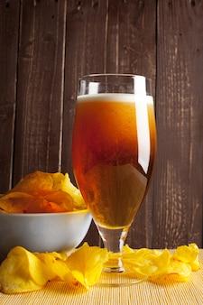 Lagerbier in den glas- und kartoffelchips auf holz