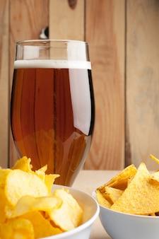 Lagerbier in den glas- und kartoffelchips auf holzoberfläche