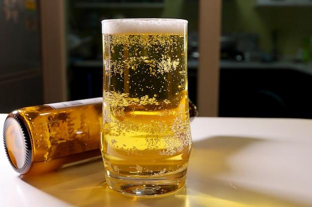 Lagerbier mit schaum im glas auf dem weißen hölzernen der gegenstange mit bierflasche.