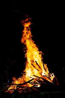 Lagerfeuer, das auf dunkler, holzbefeuerter flamme brennt.