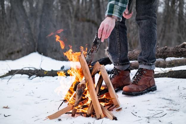 Lagerfeuer machen in einem verschneiten wald. männliche person nahe einem feuer an einem wintertag im wald