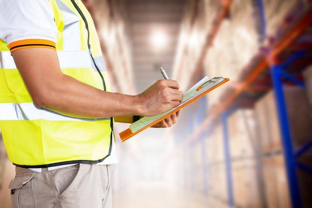 Lagermitarbeiter halten eine zwischenablage mit inventar der produkte im lager.
