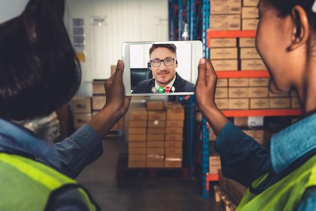 Lagerpersonal, das auf videoanruf am computerbildschirm im lagerhaus spricht