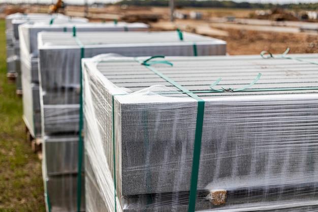 Lagerung von betonbordsteinen auf paletten auf der baustelle. vorbereitung für den einbau von betonplatten und bordsteinen. fertigwarenlager.