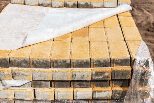 Lagerung von gehwegplatten auf paletten auf der baustelle. einbaufertige betonplatten. fertigwarenlager. Premium Fotos