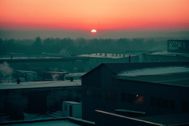 Lagerung von waren in den lagern im winter in der morgendämmerung. ansicht von oben genanntem des industriegebiets im sonnenaufgang in den rosa tönen. industriegebäudezone nah oben mit copyspace.