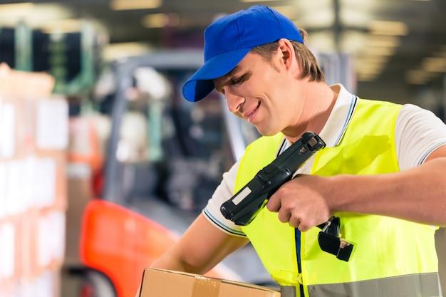 Lagerverwalter mit schutzweste und scanner scannt den strichcode des pakets und steht im lager der spedition