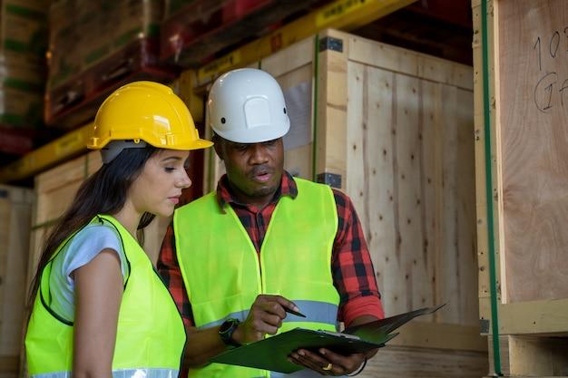 Lagerverwalter und lagerarbeiter tragen helm mit zwischenablage und prüfen produkte über lieferplan im industriellen lagerraum.